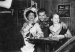 Owners of The Knotty Pine, Lil & Gus Duduse, enjoy a drink with their patrons, 1952