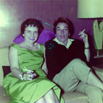 Two women sitting on a couch holding cigarettes