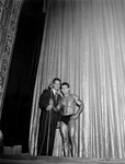 Two men standing on the stage of the Tampa Theatre