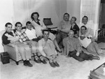 Nine men and one woman posing in a living room