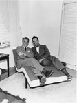 Two men reclined on a lounge chair