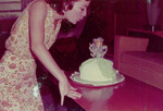 Woman blowing out candles on a doll cake