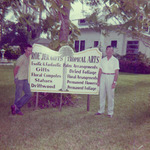 Two men standing beside a sign for Roe'Jer Gifts Tropical Arts