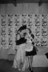 Man in drag kissing a woman on the cheek