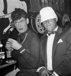 Man in drag sitting next to another man wearing a white hat