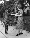 Young street vendor selling grapes to a woman in Key West