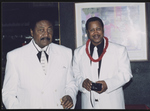 Cleveland Johnson with cigar and gentleman with camera at an event.