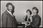 Cleveland Johnson presenting a cash prize to a man and woman.