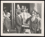 Group of people gathered for a funeral with five men carrying a white casket.
