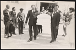Five men carrying a casket out a building, with Reverend Enoch Davis, Reverend Henry Lyons, and Reverend Wayne Thompson standing on the left-hand side.