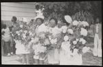 Women holding flower arrangements outside funeral at Bethel A.M.E. Church.