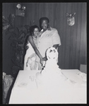 Couple embracing while cutting a wedding cake