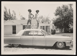 Two women standing on the roof of a car in front of R & W Wholesale