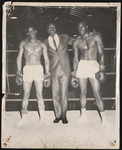 Cleveland Johnson standing in a boxing ring with two boxers