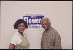 """Rene Flowers and unidentified man standing in front of a """"Rene Flowers for City Council"""" poster"""