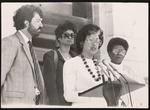 C. Bette Winbish speaking at an outside event with DEDEC Chairman, Bill Sharpe, Barbara Griffin, and DEDEC Vice Chairman, Iris Wilson, standing around her