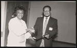Woman shaking hands with a gentleman and receiving an award from him