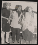 Three women singing in front of a microphone