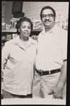 Woman and man standing in front of a grocery wall