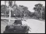 Rene Robinson seated on the hood of a car