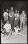 Group of young men and a young woman posing with trophies