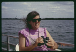 Debbie Butts binoculars on boat : Environmental Lands Acquisition and Protection Program Collection