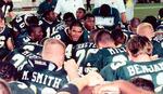 Football players huddled on sideline